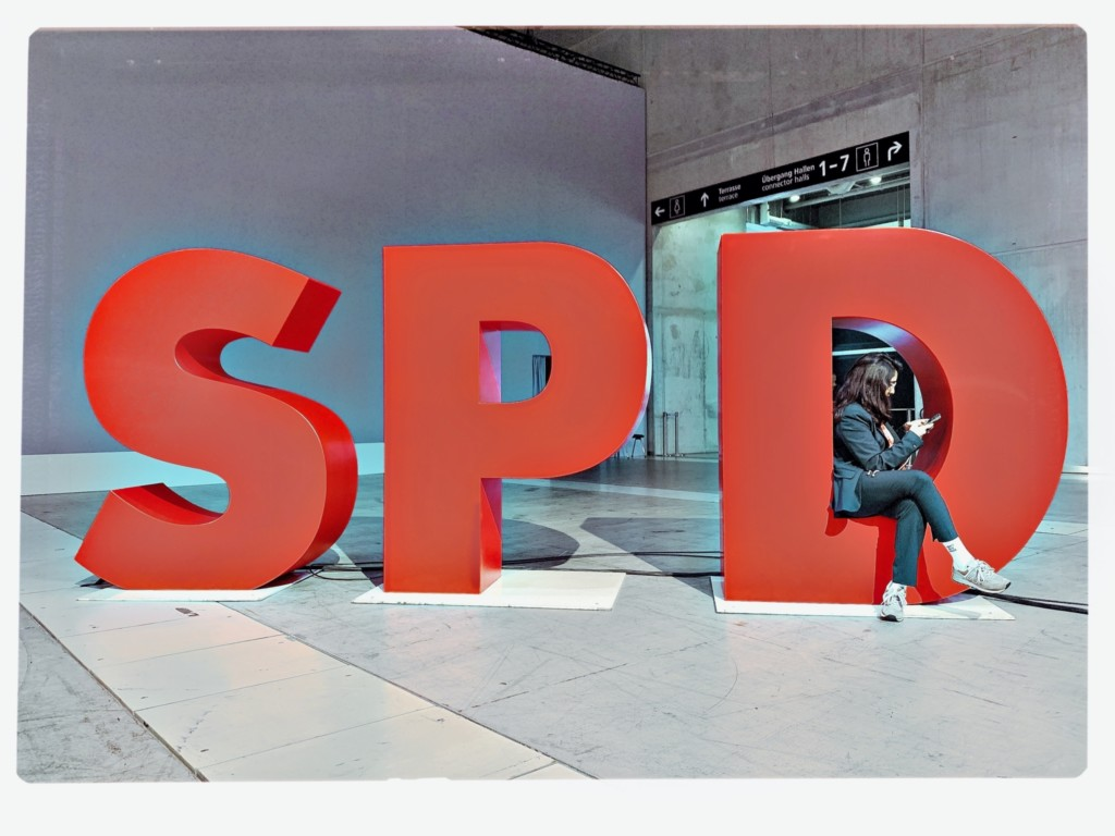 Drei große rote Buchstaben: SPD, im D sitzt eine Person mit ihrem Smartphone